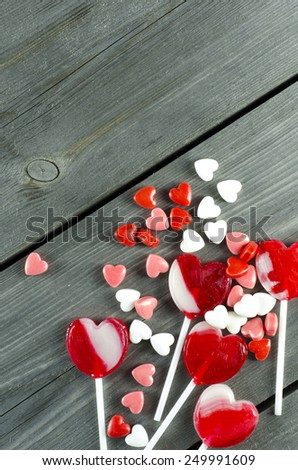 Red heart-shaped candies on wooden surface with free space