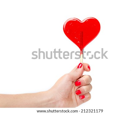 red heart shaped candy lollipop in hand - stock photo