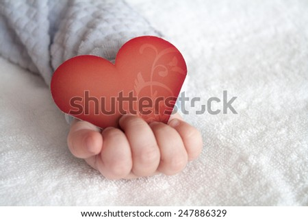 Red heart shaped card in baby hand on white soft blanket background - stock photo
