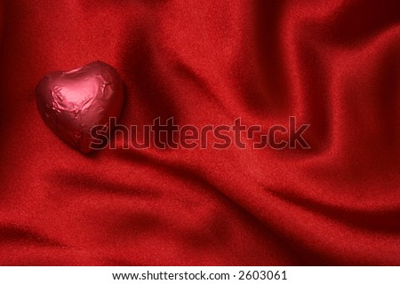 Red heart shaped foiled chocolate on red satin - stock photo