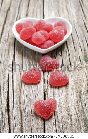 Red heart shaped jelly sweets on a rustic background - stock photo