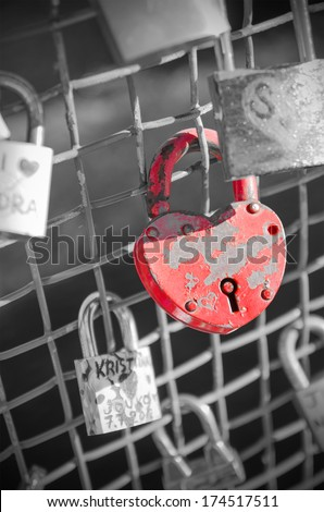 Red heart-shaped lock on a bridge - stock photo