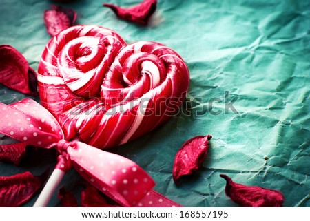 Red heart-shaped lollipop of valentines day on texture background/ Valentines day background - stock photo