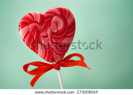 Red heart-shaped lollipop with bow over cyan background. - stock photo