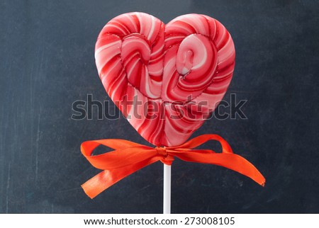 Red heart-shaped lollipop with bow over gray background. - stock photo