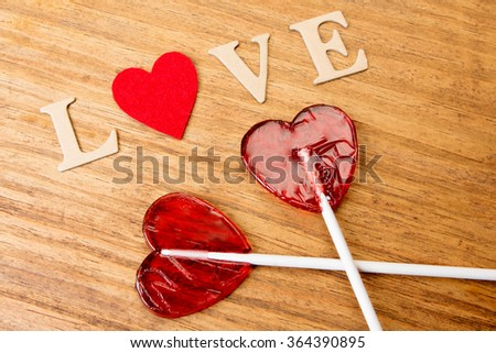 Red heart shaped lollipops on wooden background - stock photo