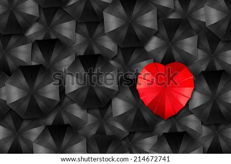 red heart shaped umbrella in middle of black umbrellas - stock photo