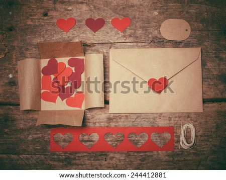 Red heart shapes, envelopes and a tag on a table ready to create a Valentine's day card - stock photo