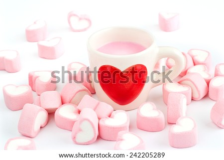 red heart symbol on strawberry milk cup and pink candy heart on white background