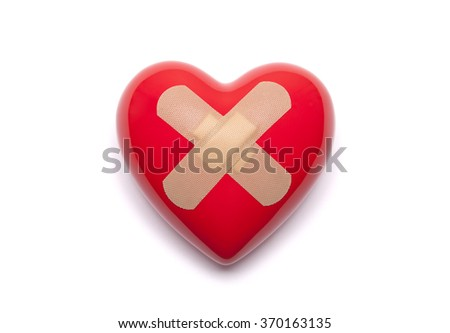 Red heart with bandages on white background - stock photo