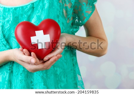 Red heart with cross sign in female hand, close-up, on light background - stock photo