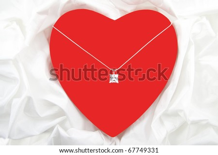 Red heart with diamond on necklace isolated over satin - stock photo