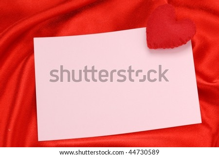 Red heart with empty note on red silk