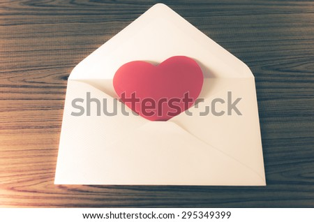 red heart with pink envelope on wooden background vintage style - stock photo