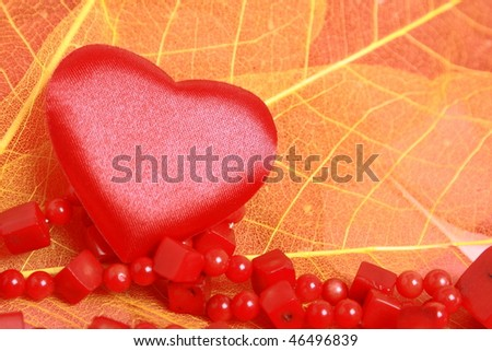 Red hearts and coral beads on leaves - stock photo