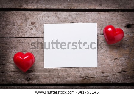Red hearts  and empty tag on aged wooden background. Selective focus. Place for text. - stock photo