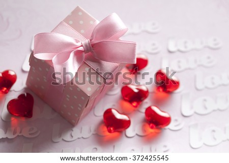 Red hearts and gift box on pink background