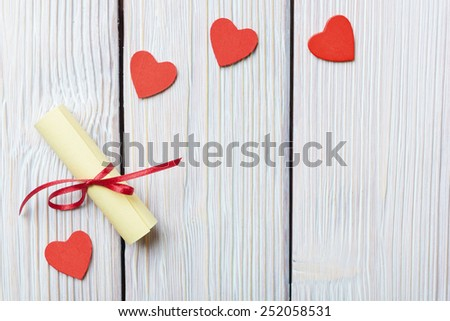 Red hearts and rolled paper on vintage wooden background - stock photo