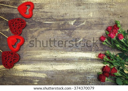 Red hearts decoration with red  beautiful roses on old wooden texture background, valentines day card concept. Old wooden table with texture.
