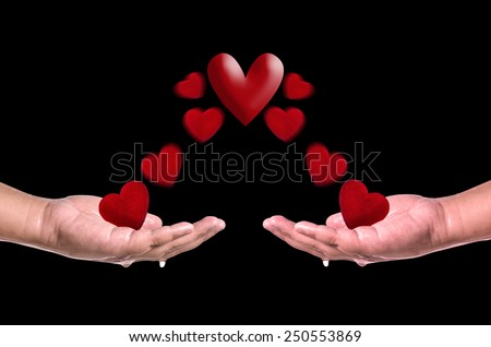 Red hearts fly into hands on black  background . Love concept - stock photo