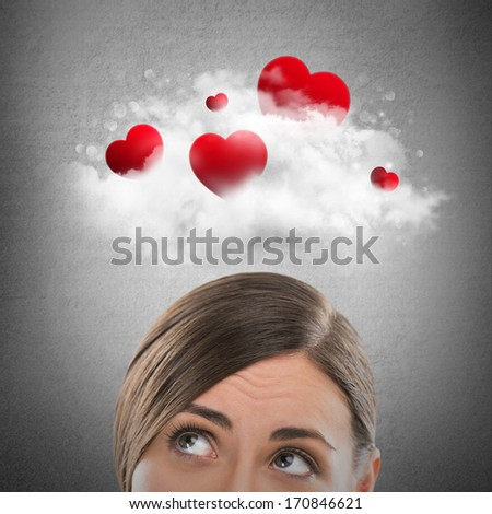 Red hearts flying in cloud overhead of beautiful dreamy woman. Valentine's day background - stock photo