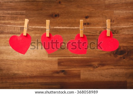 Red hearts hanging on line on wooden background. Valentines day decoration. - stock photo