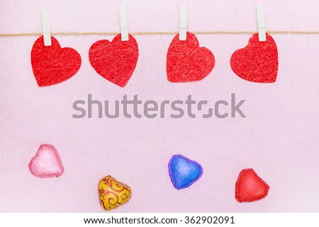 Red hearts hanging on rope on white clothespins with several sweet chocolate hearts on pink background