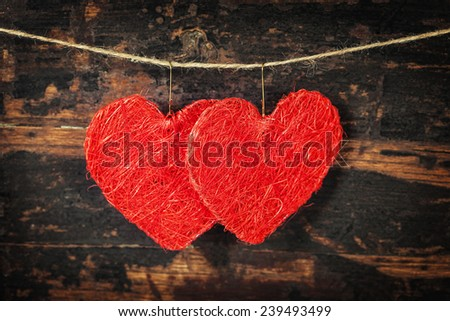 Red  hearts  hanging on the clothesline. On old wood background - stock photo