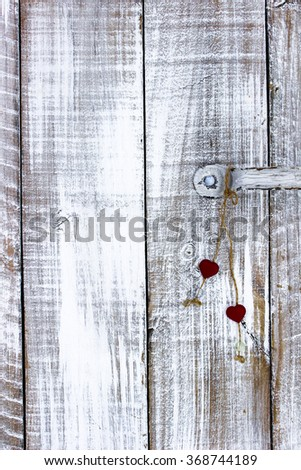 Red  hearts hanging on white painted rustic antique wooden door; Valentine's Day and love concept - stock photo