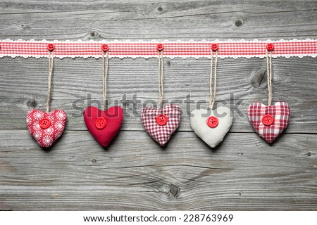 Red hearts hanging over old wood background - stock photo