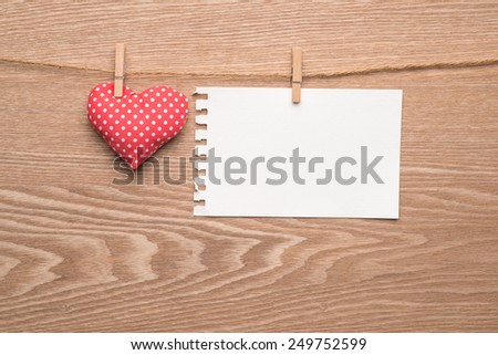 Red hearts hanging over wood background with paper. Copy space. Image of Valentines day. - stock photo