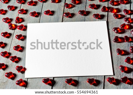 Red hearts made of glass on wooden background. White sheet of paper as a free space for text.