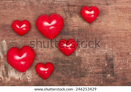 Red hearts on old shabby wooden background - stock photo