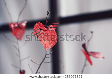 Red hearts on the branches with checkered ribbons - stock photo