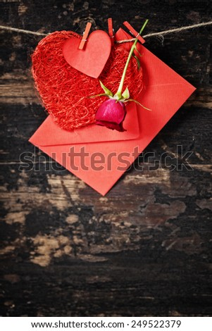Red  hearts, rose and envelop  hanging on the clothesline. On old wood background - stock photo