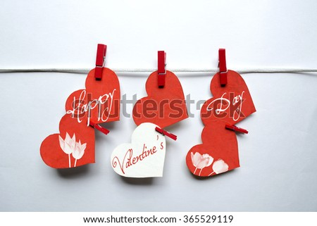 Red hearts with clothespins hanging on clothesline on white background. Romantic date, love Valentines Day concept - stock photo