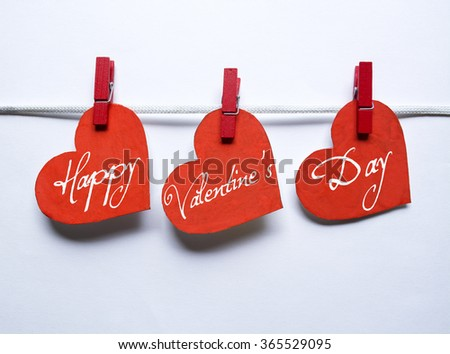 Red hearts with clothespins hanging on clothesline on white background. Romantic date, love Happy Valentines Day concept - stock photo