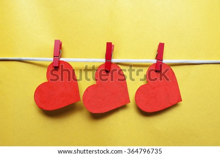 Red hearts with clothespins hanging on clothesline on yellow background. Romantic date, love Valentines Day concept - stock photo