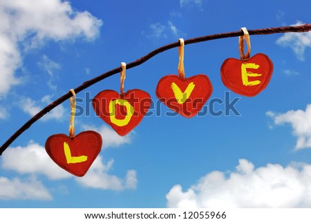 Red hearts with letters LOVE written in them hanging in the air - stock photo