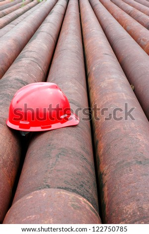 red helmet miner oil on an iron pipe in an oil mining area - stock photo