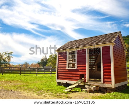 red hen house on an autumn afternoon - stock photo