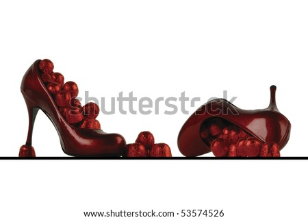 Red high heel shoes isolated on white full of chocolates - stock photo