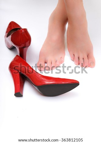 Red high heel shoes on the ground with barefoot girl on background - stock photo