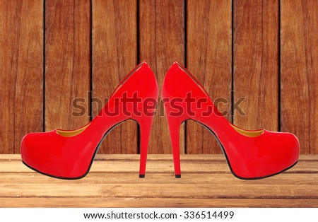 red high heeled woman shoes on wooden table background - stock photo