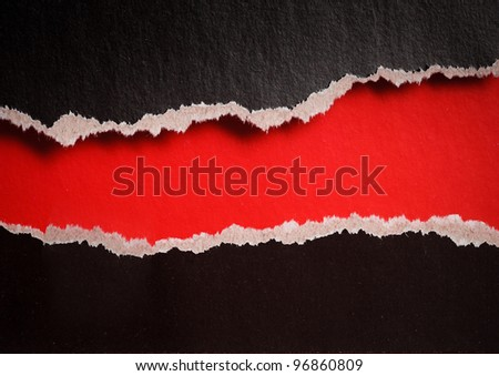 red hole with torn edges in black paper - stock photo