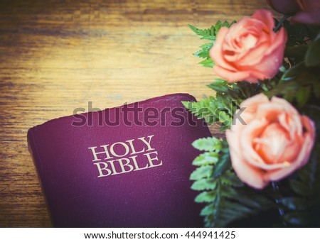 Red holy bible with burred of roses on wooden background, copy space - stock photo
