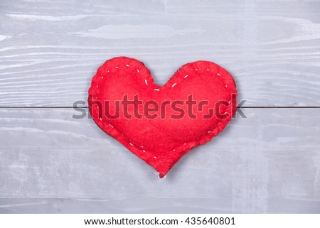 Red homemade valentine's day heart natural grey wooden background copy space.