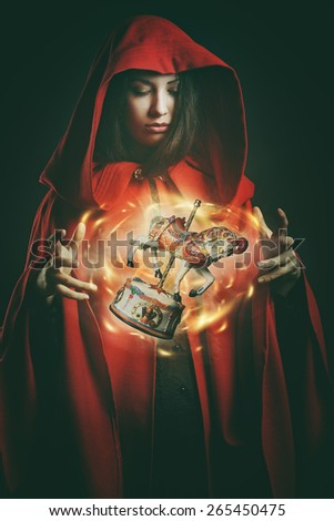 Red hooded woman with magical wooden toy . Fantasy and surreal - stock photo