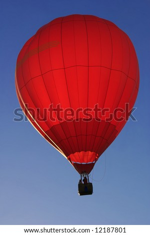 Red hot air balloon illuminated by sunrise against blue sky - stock photo