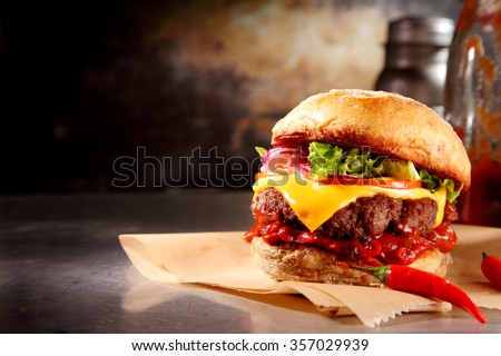 Red hot chili cheeseburger with a spicy chilli pepper sauce and melting cheese over a juicy beef patty on a crusty bun served on brown paper, with copyspace - stock photo